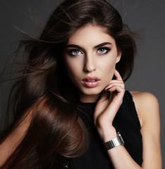 beautiful girl with dark hair and bright makeup in elegant dress
