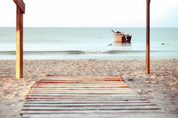 Empty wooden table or shelf wall with view of sunset or sunrise and boat on sand beach background. For present your products.