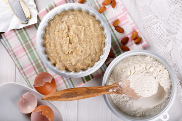 Raw batter for almond cake and ingredients for baking