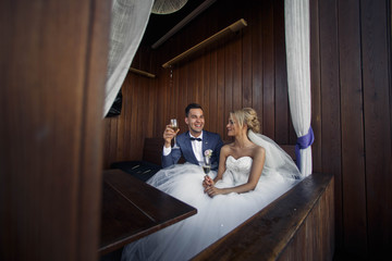 young groom and bride drink Champagne