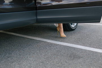 Elegant shoe on the leg of the bride in the car