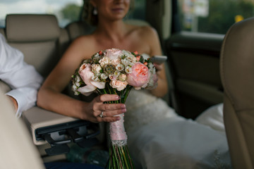 Bride with the beautiful bouquet in the wedding car