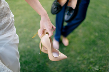 Bride is holding a beige wedding shoes