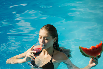 woman with watermelon and wine in pool