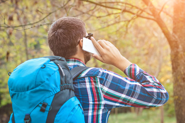 Man tourist is using a smartphone. Caucasian male outdoors in nature. Hiker young man with backpack