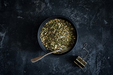 Dry herbal tea in black ceramic bowl with tea spoon on dark background. Top view, horizontal, toned image. Healthy lifestyle concept