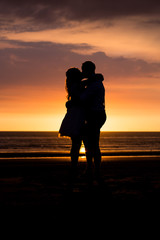 Love couple silhouette during sunset at the beach
