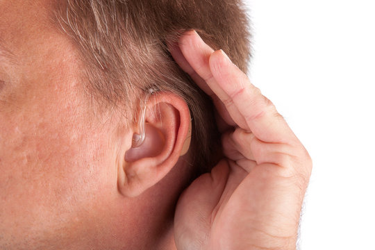 Man wearing hearing aid cupping his hand behind his ear
