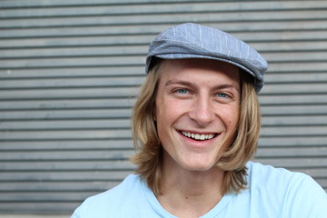Portrait of a smiling Caucasian man in newsboy hat looking to camera with copy space
