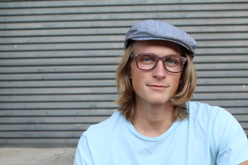 Close up of long haired blond male wearing glasses and news paper boy hat with copy space on the left