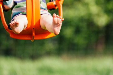 Focus on toddler girl's feet and legs as she swings in an orange baby swing at a playground