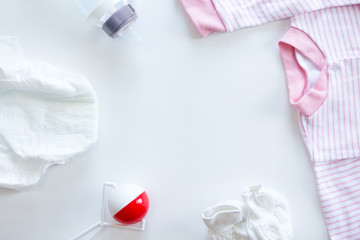 Set of baby supplies on the white table: diaper, beanbag, bottle, pink striped suit. Top view, copyspace in the middle