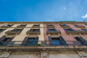 yellow & red Vintage building with blue sky clouds at summer day in Spain