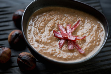 Close-up of chestnut cream-soup topped with smoked meat
