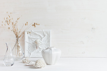 Soft home decor. Seashells and glass vase with spikelets   on  white wood background. Interior.