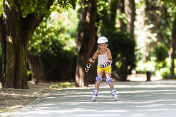 Little girl on inline skates with full protective equipment