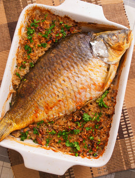 Baked carp in casserole with rice. Vertical shot