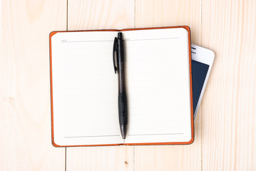 Small notepad with pen and smartphone