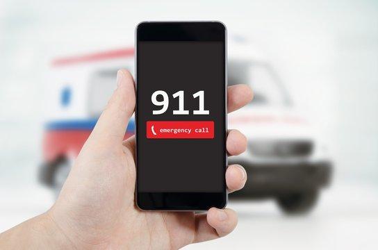 Man calling emergency. Ambulance in background.
