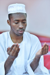 African Muslim Man Making Traditional Prayer To God While Wearing A Traditional Cap Dishdash