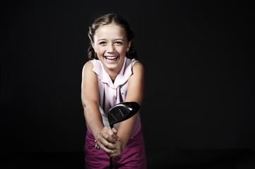 Teenage girl posing with golf club