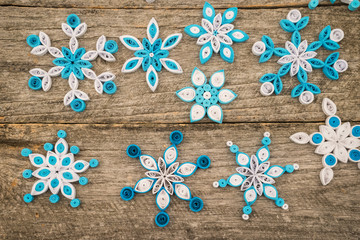 Paper snowflakes made with quilling technique on a wooden surface