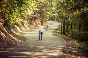 Skateboarder standing in the middle of the road in the forest and raising his hands up