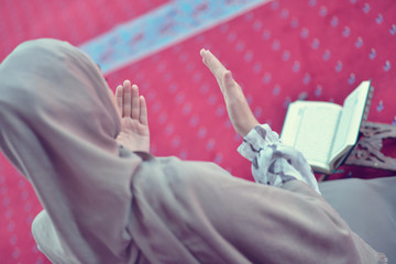 Young muslim woman praying in mosque