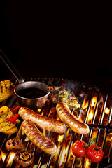 Grilled sausages besides peppers and tomatoes