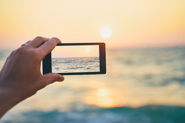 Cell technology and vacation. Close up of male hand holding smartphone, taking picture of sea sunset.