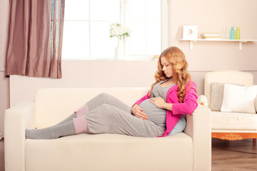 Beautiful Pregnant Woman Resting on the Sofa at Home