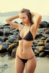 Sexy beauty and beach fashion. Outdoor portrait of beautiful young woman with long hair in black bikini.