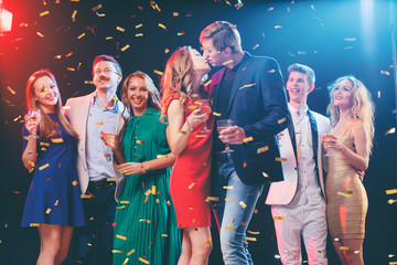 Party and celebration. Couple kissing. Group of seven happy smiling friends having fun together among confetti in night club.