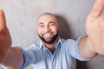 I love selfie! Handsome young latino man in shirt holding camera and making selfie and smiling while standing against grey wall.