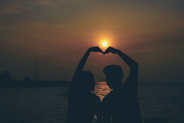 Silhouettes of hugging couple against the sea at sunset.