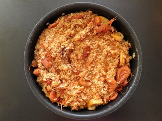 paella in the pot on a black background