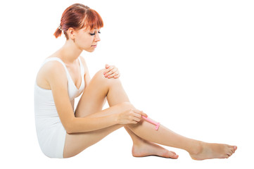 Red, beautiful girl shaves legs pink shaver On white, isolated background.