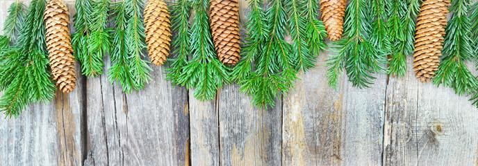 Weihnachtliche Bordüre mit Tannenzweigen und Tannenzapfen auf altem Holz, Panorama, Copyspace
