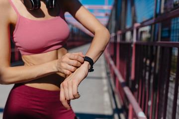 Beautiful Fit Female Runner Using A Sportwatch . Williamsburg Bridge Brooklyn NYC
