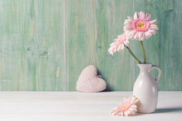 Pink Gerbera flowers in vase on wooden background