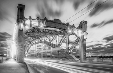 Black and white envelope size view of white night car traffic through the famous Saint Petersburg bridge named after Peter the Great