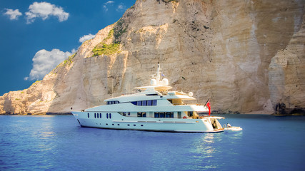 Luxury white yacht navigates into beautiful blue water near Zakynthos island. View from the top of a large white yacht at Navagio Beach.