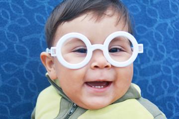 Smiling baby boy wearing glasses