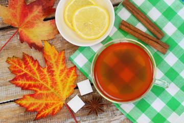 Colorful autumn leaves and lemon tea on checkered cloth