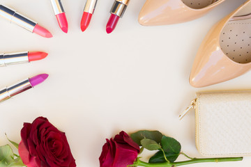 Nude colored high heels with lipsticks, fresh rose flowers and wallet hero header