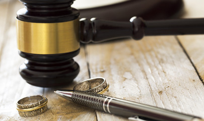 Divorce concept. Close up of wedding rings and judge gavel
