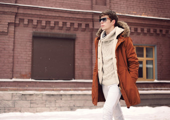Wall Mural - Fashion stylish man wearing a jacket and sunglasses walking in c
