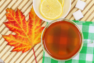 Glass of tea, autumn leaf and lemon