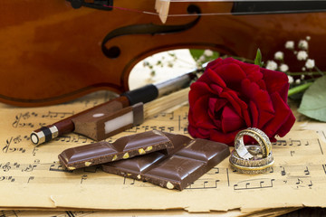 Marriage rings, red rose, chocolate chips and violin on music notes