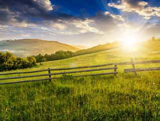 wooden fence on hillside at sunrise